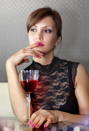 beautiful woman in black dress on sofa with glass of wine photo