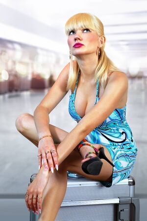 young beautiful blonde girl sits on bag at airport photo