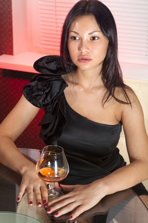 beautiful woman in black dress on sofa with glass of brandy Stock Photo