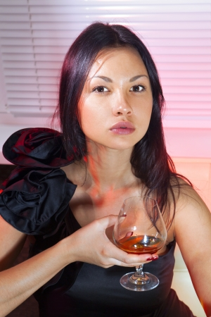 beautiful woman in black dress on sofa with glass of brandy Stock Photo - 15206556