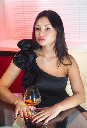 ladylove: beautiful woman in black dress on sofa with glass of brandy Stock Photo