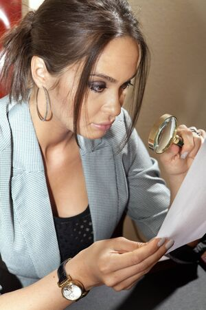 boffin: business woman looks on one document by magnifying glass