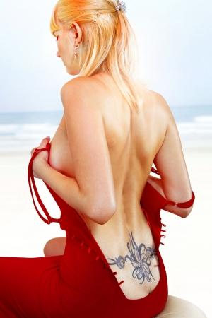 tatouage sexy: femme en robe rouge avec le tatouage sur son dos assis près du rivage de la mer Banque d'images