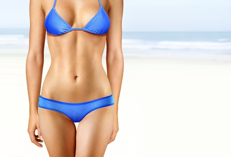 body of woman in blue bathing suit on beach photo