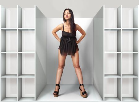 checkroom: beautiful woman fits on a black dress in fitting-room Stock Photo