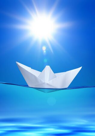 vessel sink: white paper toy-ship on the blue water under sun Stock Photo