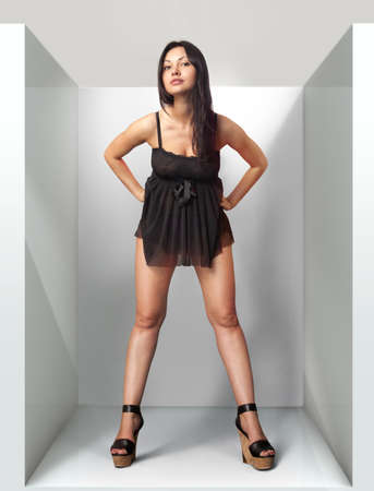 forepart: beautiful woman fits on a black dress in fitting-room Stock Photo