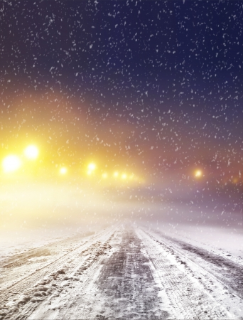 Snow covered winter road with shining streetlights at night photo