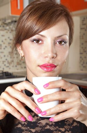happy brunette in cafe at little table with cup of coffee Stock Photo - 17346114