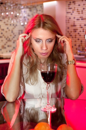 ladylove: sad beautiful woman in kitchen with glass of wine