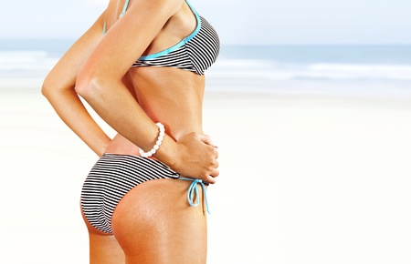 bathing   suit: body of woman in blue bathing suit on beach Stock Photo