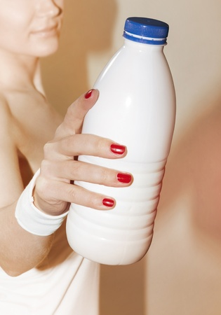 kefir: close up of female hand that suggests to take bottle of milk