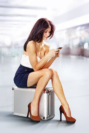 young beautiful traveler with mobile phone in airport photo