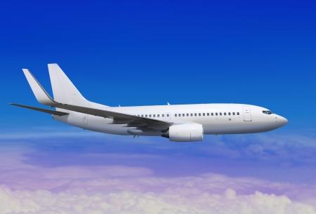 postponed: white passenger aircraft in the blue sky landing away Stock Photo