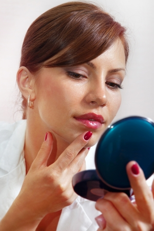 beautiful face smartens up in front of compact mirror Stock Photo - 20410887