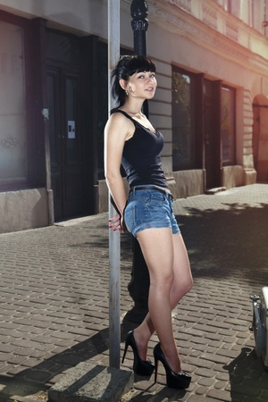 beautiful woman stands near wall of building, hitchhiker Stock Photo