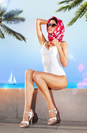 a bathing place: woman in white bathing suit and red scarf on embankment of resort place Stock Photo
