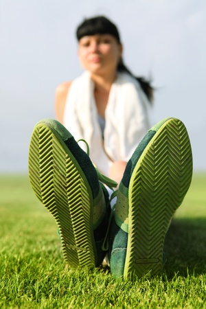 vacationer: green sole of shoes on grass, tired sportswoman