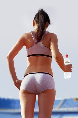 sexy shorts: sportswoman who holds bottle of water at stadium