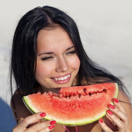 vacationer: smiling girl eats slice of juicy ripe watermelon Stock Photo