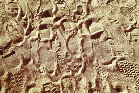 indentation: prints from various footwear on sand, background Stock Photo