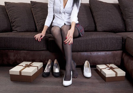 lady trying on several pairs of new shoes in the mall photo