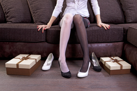 personal shopper: lady trying on several pairs of new shoes in the mall
