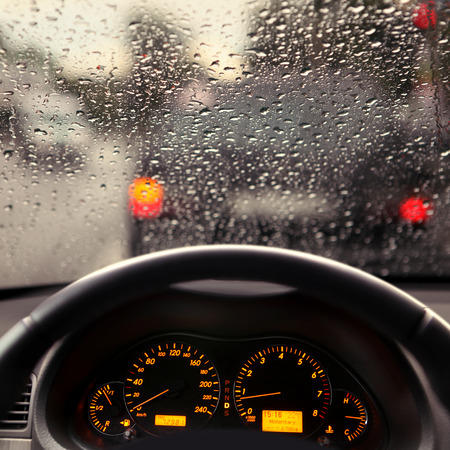 dashboard and rain droplets on car windshield