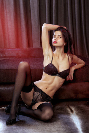 beautiful sexual woman sits near sofa in black underwear photo