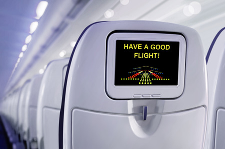 airplane landing: Passenger seat of plane with screen. Have a good flight!