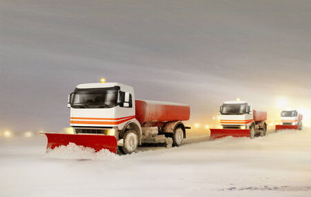 plough: Snowplow Trucks Removing the Snow from the Highway during a Cold Snowstorm Winter Day