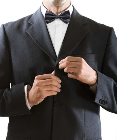jazzbow: hands of the man who in a black tuxedo clasps a jacket button