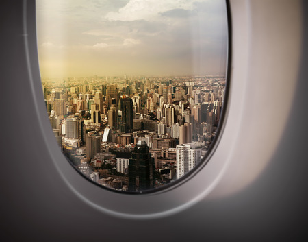 a window on the world: beautiful city view of Bangkok with blue sky from plane window