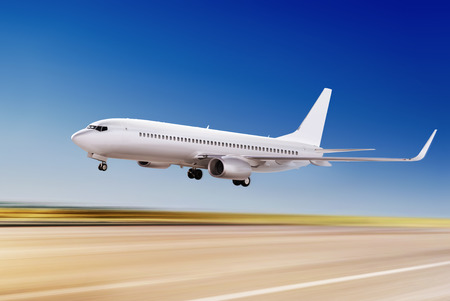 strips away: white passenger plane is flying up from airport