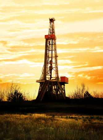 oil pollution: Natural gas production land drilling rig at sunset. Stock Photo