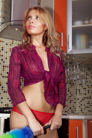 empleada domestica: criada atractiva triste con el plumero en la cocina Foto de archivo
