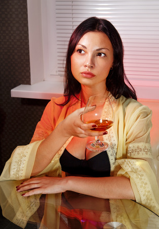 ladylove: beautiful ladylove in dress on sofa with glass of brandy