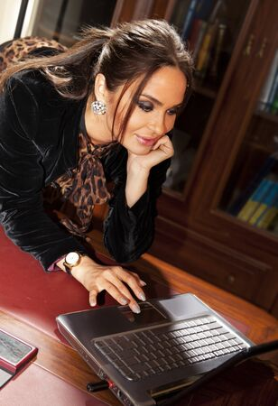 uses a computer: Happy woman uses laptop computer in office