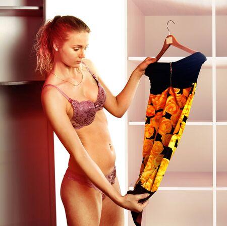yelow: beautiful woman fits on yelow dress in the shopping mall Stock Photo