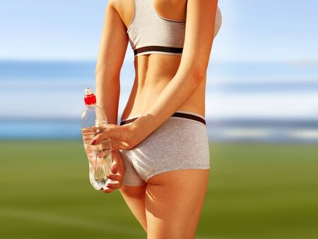 thirst: sports woman who holds bottle of water at stadium