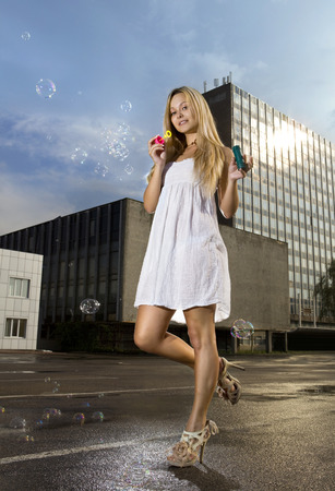thoughtless: young blonde woman blowing soap bubbles on a street of city