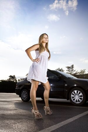 supercilious: ambitious girl in a white dress near the black car