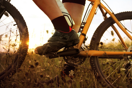 extreme sports: foot of traveler who stopped on field at sunset time