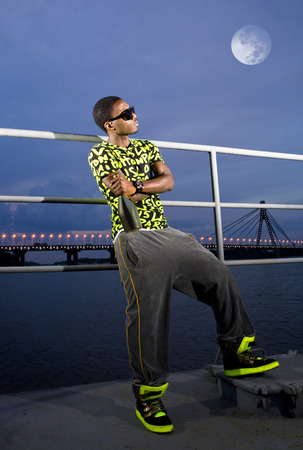 rapper: blacky rapper on quay with bottle of champagne in the bright of the moon Stock Photo