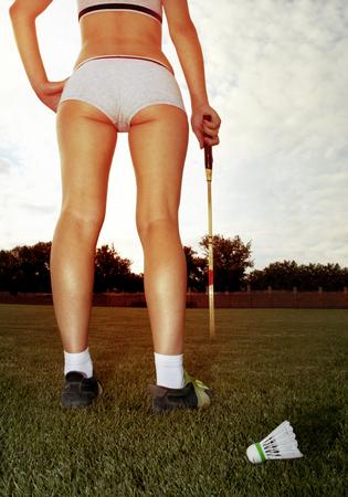 pies sexis: largas piernas de mujer que juega al bádminton en el césped Foto de archivo