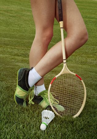 recreate: foot of woman who plays badminton on grass