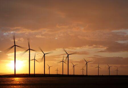 日没で電気を生成する風力タービンのシルエット