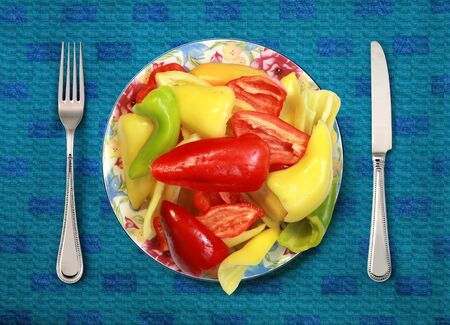 bell peppers: bell peppers on plate, knife and fork on table Stock Photo