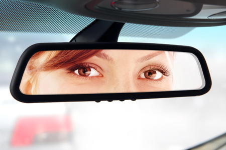 female driver: woman sits on drivers seat and Looks in the rear-view mirror