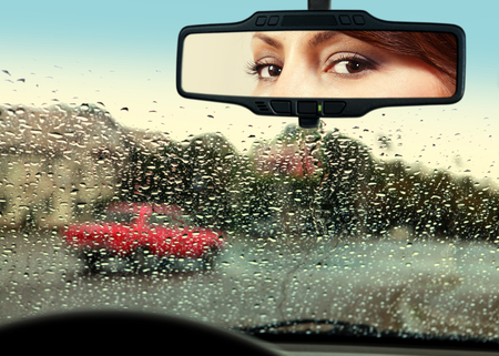 drivers seat: woman sits on drivers seat and Looks in the rear-view mirror